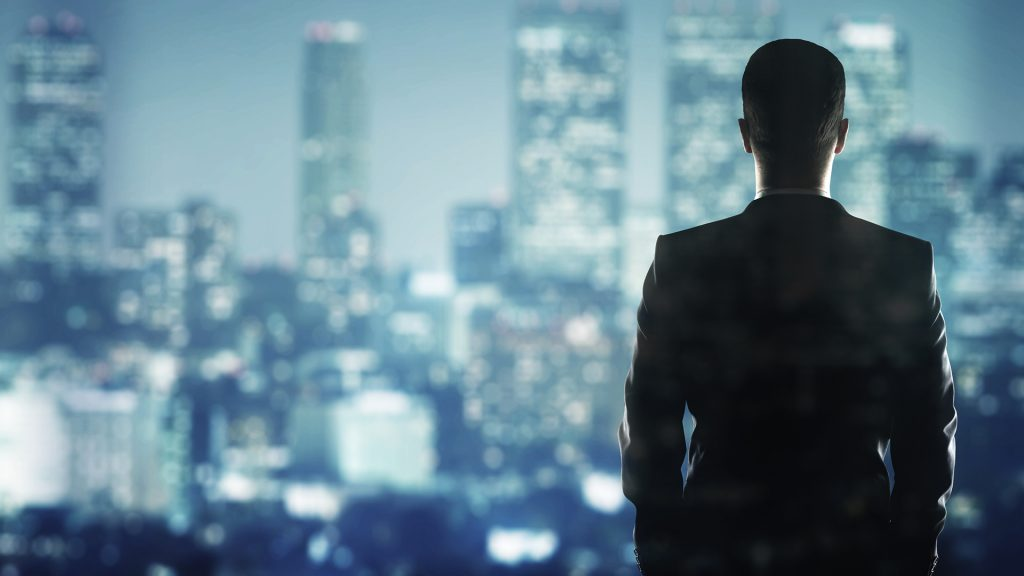 man in office looking out of the window at night