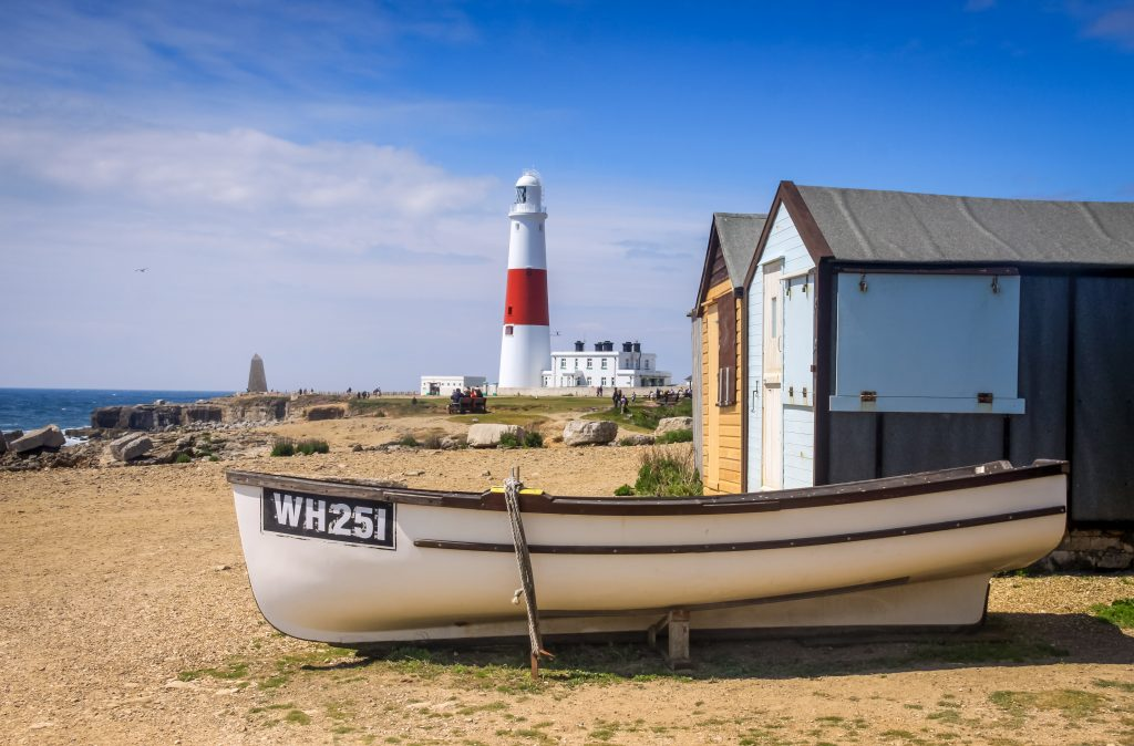 Boat, Beach Huts and Portland Lighthouse